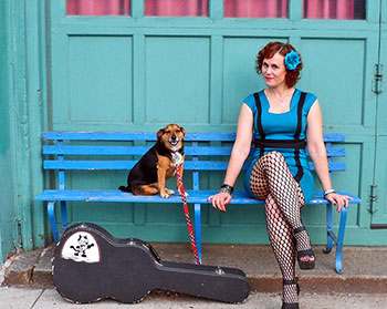 Photo of Erin Harpe, guitar case and dog