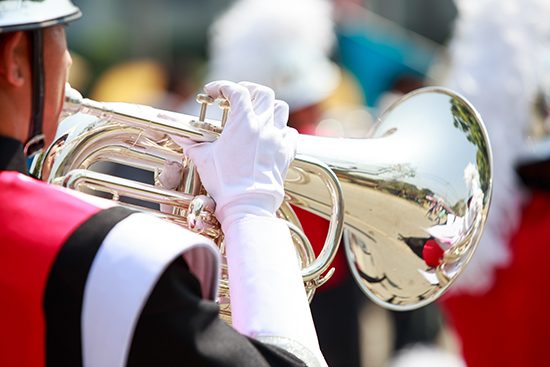 man in a band uniform playing a wind instrument