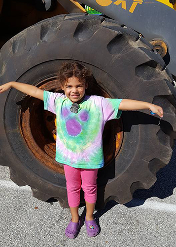 Child measures herself against tractor wheel