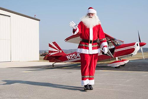 Santa Claus walking away from an airplane.