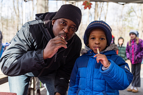 Father and son enjoy freshly tapped maple syrup