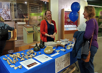 Archaeologist at table with artifacts
