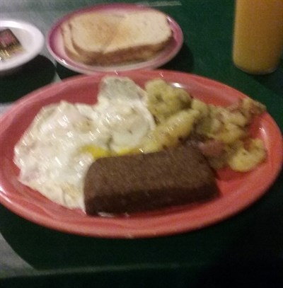 Fried eggs, scrappple, home fried potatoes, toast and juice. -