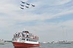 People watch the Blue Angels fly from the water.