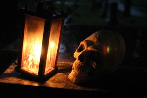 Historic lantern with skull on antique table