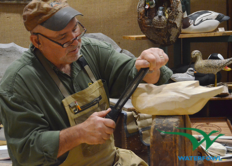 A waterfowl artist carves in his studio