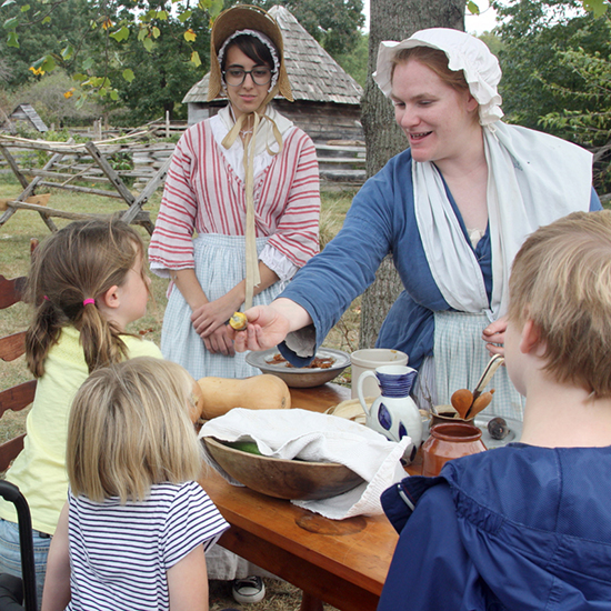 Historians in period dress explain food from the 18th century