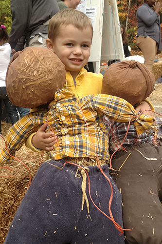 young boy with his new scarecrow friends