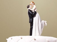 A bride and groom statue on a cake.