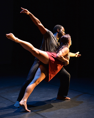 A male and a female dancer on a black stage.