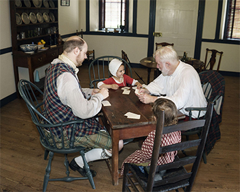 Two men and two children play card games