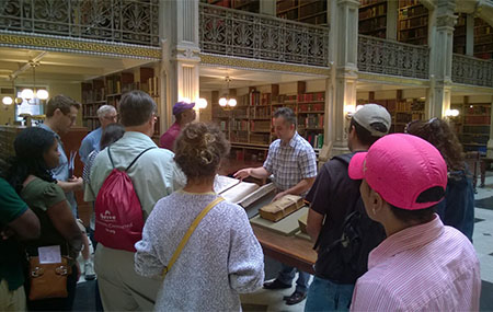 Guide Paul Espinosa with a tour group at Peabody Library.