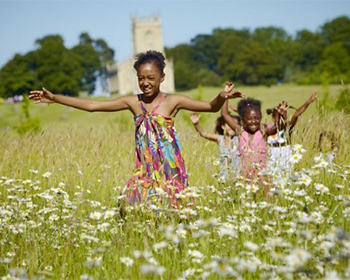 Children play in a field for Earch Day