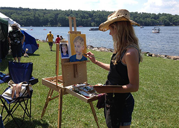 An artist painting at Art in the Park