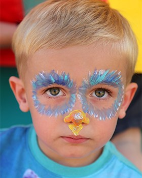 A little festival-goer shows off his painted face