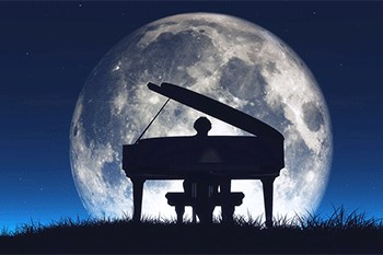 A piano player at night plays during a full moon
