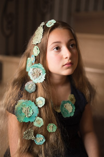 A girl with paper lichen in her hair.