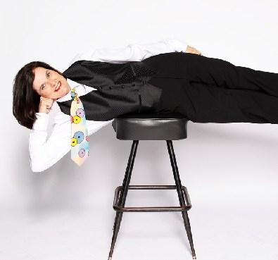 photo of paula poundstone laying sideways on a stool