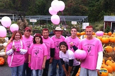 People in pink with plants, pumpkins