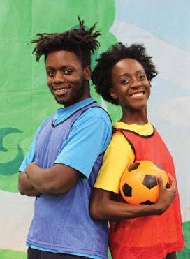 Two friends smiling and holding a soccer ball