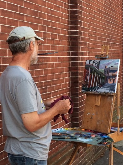 Artist, Jim Rehak painting in downtown Berlin