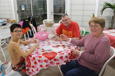 A family enjoys making Valentine's Day crafts.