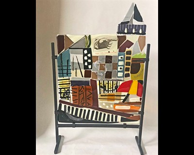 Fused glass piece depicting city life.