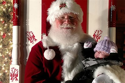 Santa holds a baby at Christmas on the Square