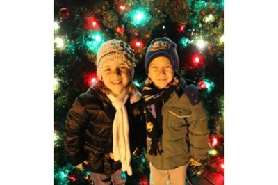Children stand by a Light up the Town tree