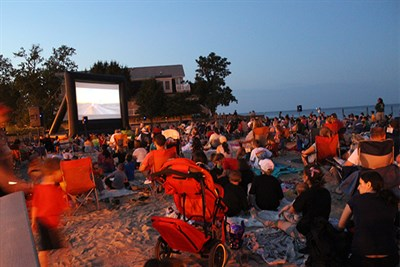 People gather to watch a movie on the beach