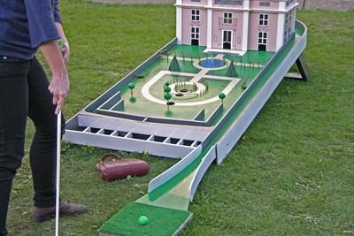 Man plays mini golf on an elegant course