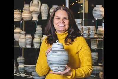 An artist holding pottery