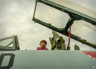young child looks into a pilot's cockpit controls