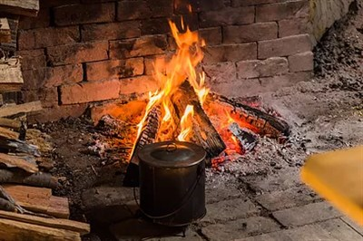 a large pot over a wood fire