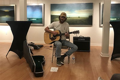 A musician plays in front of paintings at Originals Only night