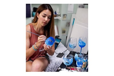 A woman paints a wine glass at Brushes and Bubbly