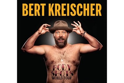 Bert Kreischer bare chested with a hat on his head