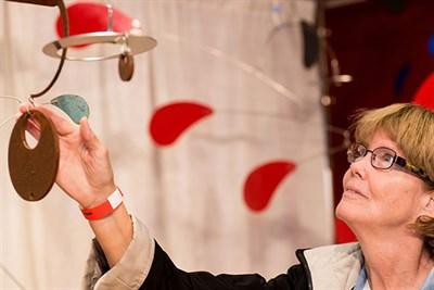 A craft show visitor admires artwork