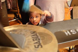 A young audience member tries out the instruments