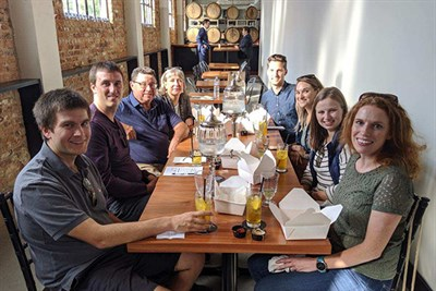 Tour group with craft cocktails at Tenth Ward Distilling Co