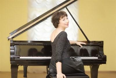 Elena Kuschnerova sitting at black piano
