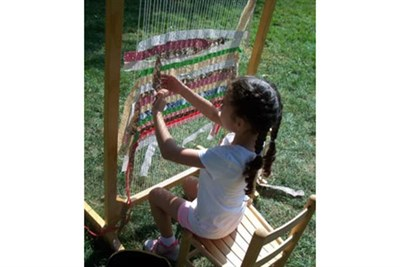 Young weaver tries her hand with a colonial style loom