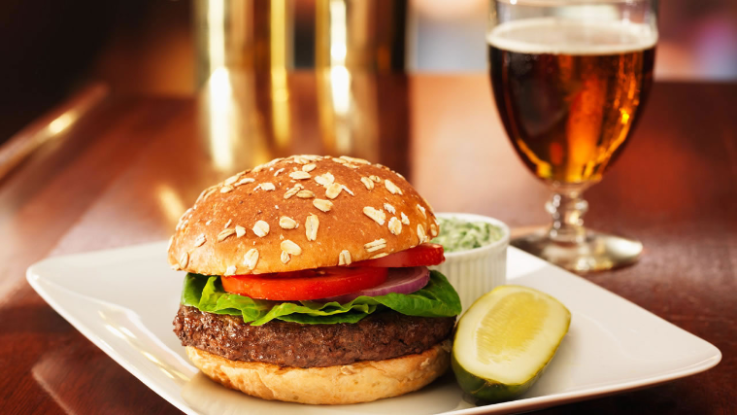 A tasty burger with tomato, lettuce and onion joined with a pickle, cole slaw and a cold beer.