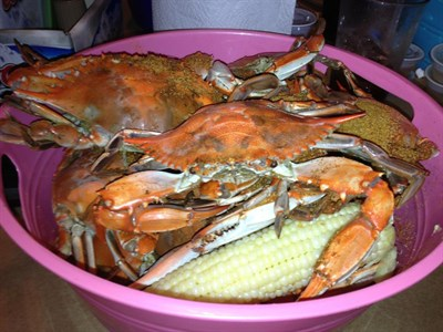 A pink plastic basket of steamed crabs and white sweet corn.
