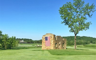 Picture of a fairway that has a stone wall with an American flag hanging along the side.